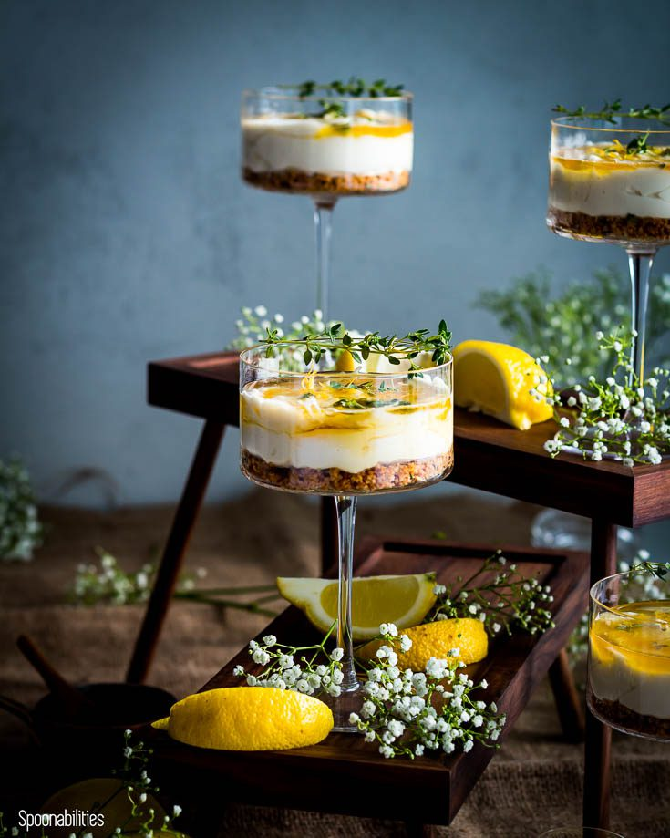 One high rise stand with a cheesecake in a cocktail glass and another high rise stand in the back with two cocktail glasses with the no bake cheesecake. Spoonabilities.com