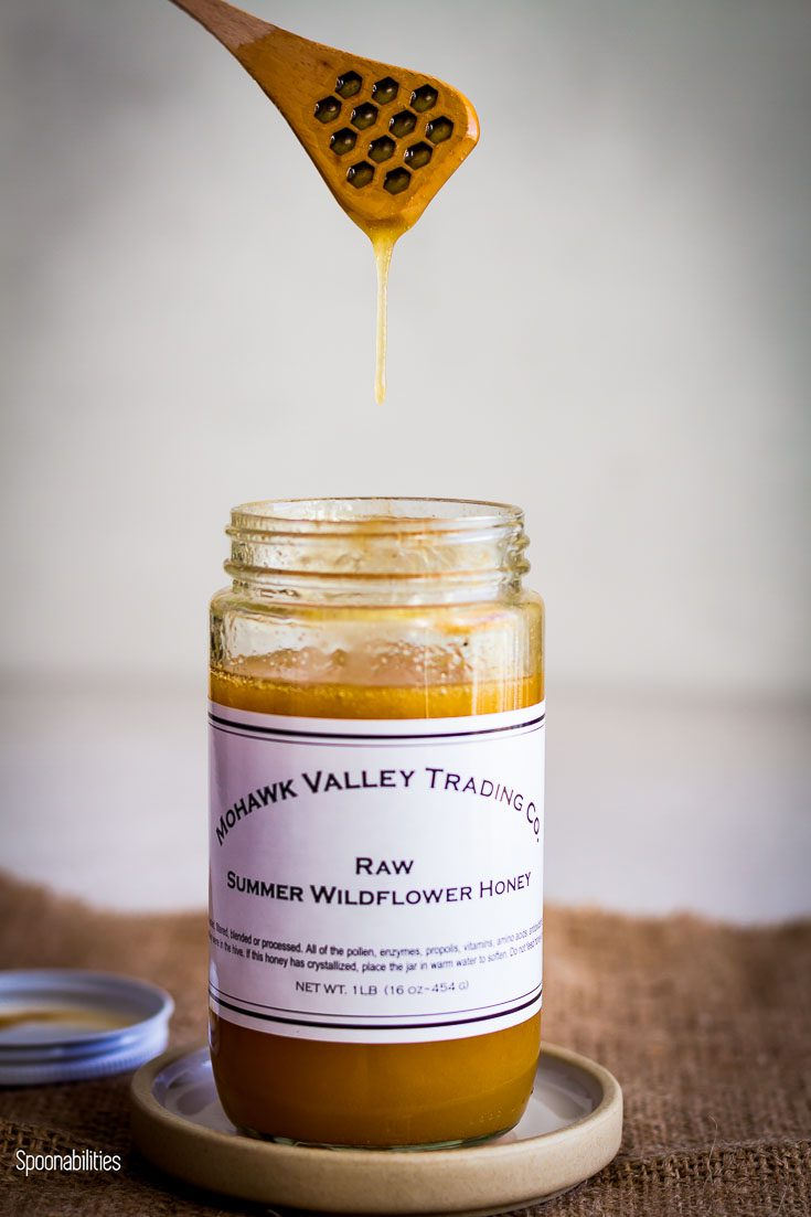 Open jar of Raw Summer Wildflower Honey and one hand with a honey dipper in the air dripping honey into the jar. Spoonabilities.com