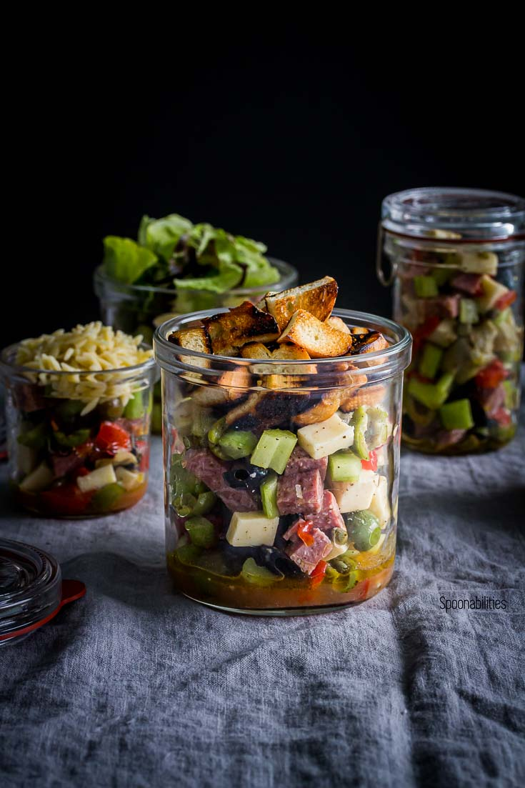 A Jar in the center with salad topped with croutons and three jars in the background. Spoonabilities.com