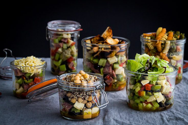 Six variation salad in Jar filled with Antipasto, pasta, quinoa, lettuce, orzo & cubed bread. Spoonabilities.com
