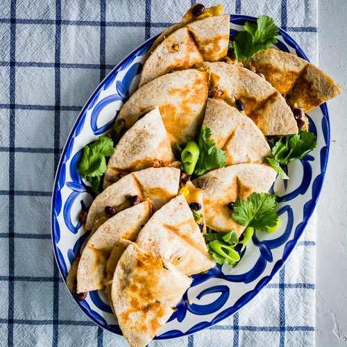 Veggie Quesadillas served in a blue & white oval serving plate on top of a white napkin with blue stripes. Spoonabilities.com