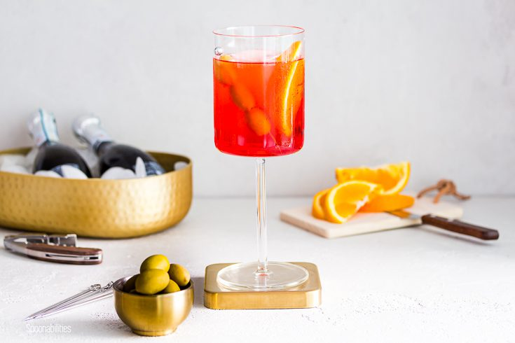 Tall cocktail glass in the center with the Italian drink Aperol Spritz with green olives. In front of the glass a small golden bowl with Greek olives and in the background two bottles of prosecco and orange slices. Spoonabilities.com