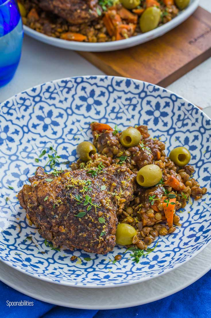 Blue and white bowl with braised Chicken thighs, lentils & carrots. Garnished with Green olives, lemon-thyme herbs & lemon zest. Spoonabilities.com