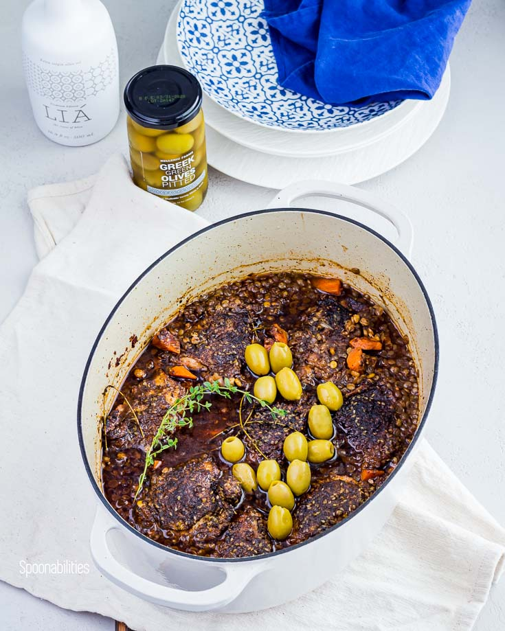 Lodge white oval Dutch oven pot with chicken thighs, lentils, carrots with Greek olives. In the background a jar of Pitted green olives and Greek premium Lia extra virgin olive oil. Spoonabilities.com
