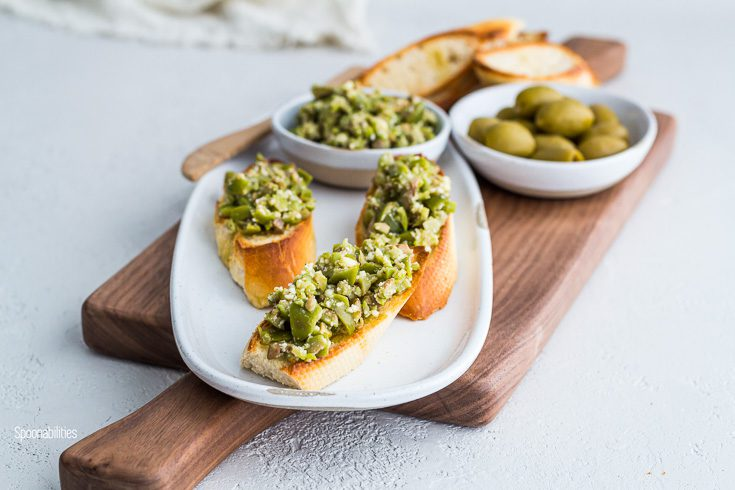 Narrow oval plate with three crostini with crushed green olives with Parmesan, garlic & olive oil. Spoonabilities.com