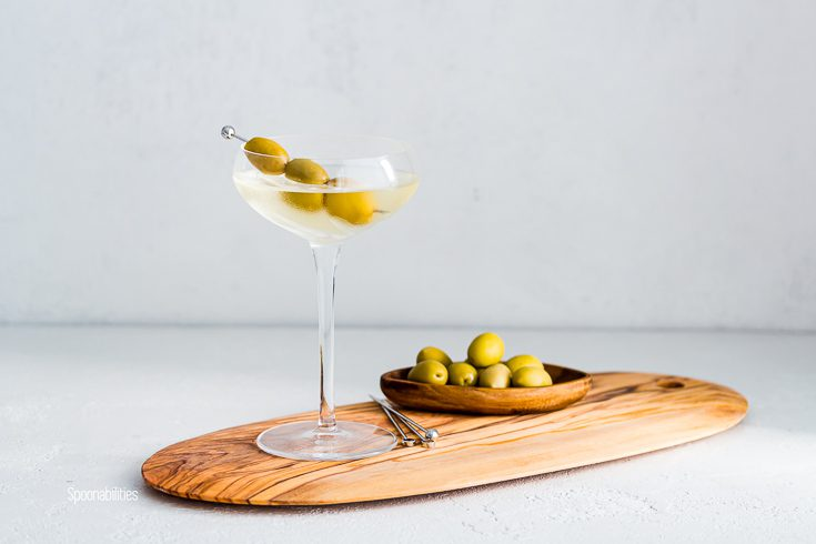 A Cocktail glass on top of a wooden board with the drink dirty martini and garnished with three olives in a metal pick. In the background pitted green olives in a small oval wooden bowl. Spoonabilities.com