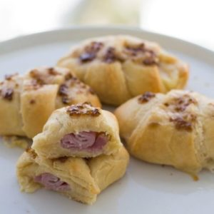 half cut ham and cheese crescent roll on plate with 3 other full rolls