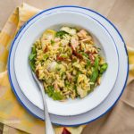 White pasta plate with blue rim with Mediterranean Orzo Salad is easy, light, and packed with flavorful ingredients like tuna, artichokes, sun-dried tomatoes, capers and a lemon Dijon Mustard Dressing