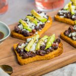 Four Avocado & Black Bean Crostini recipe on a wooden board. Spoonabilities.com