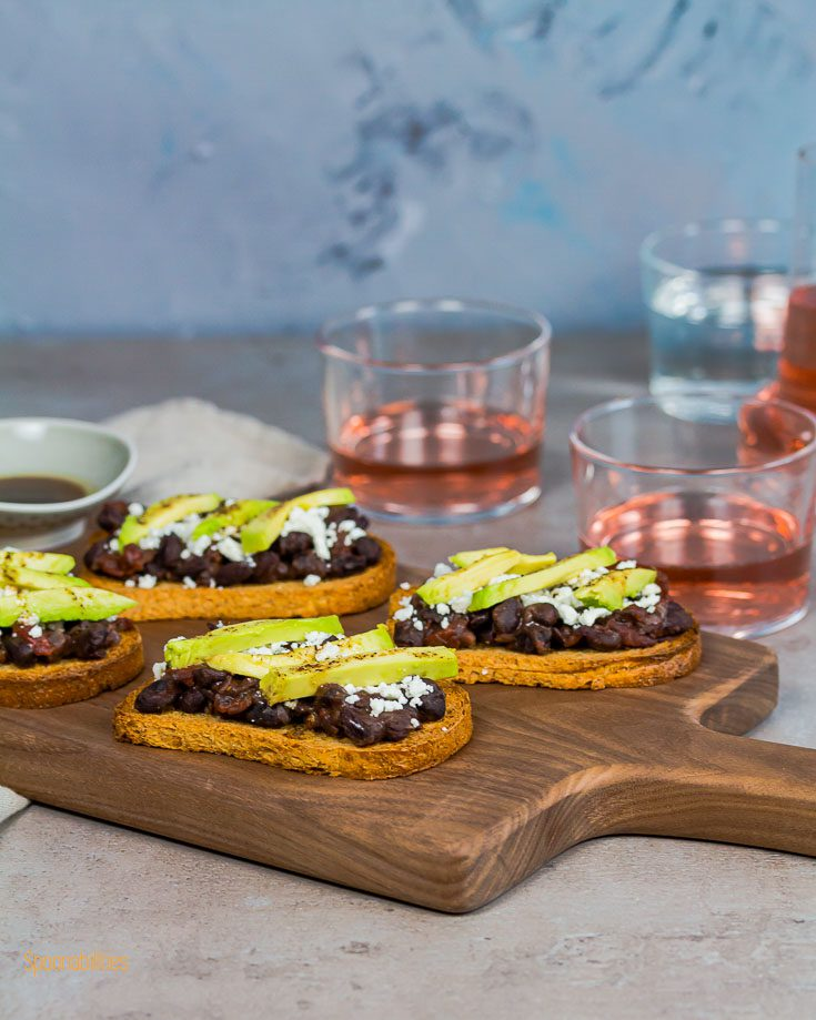Four Crostini in a wooden board with two glasses of Rose wine. Spoonabilities.com