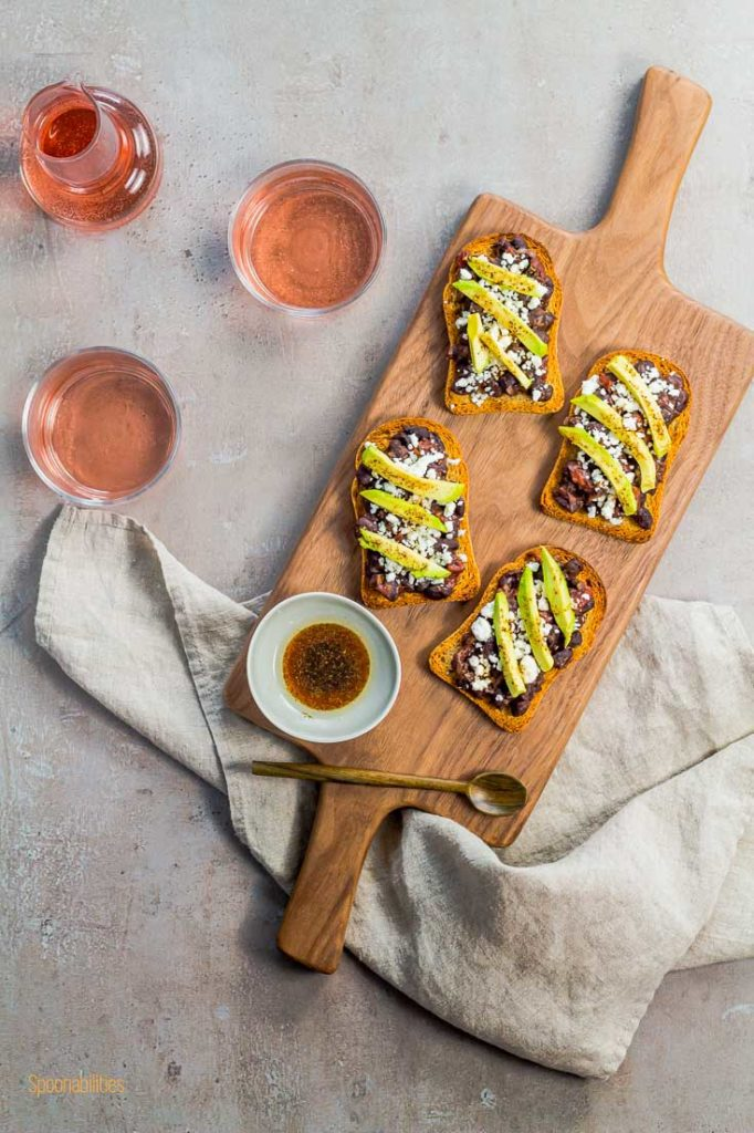 Flat lay photo of four crostini in a wooden board with a small sauce bowl in the bottom left side and a glass of rose wine on the left side. Spoonabilities.com