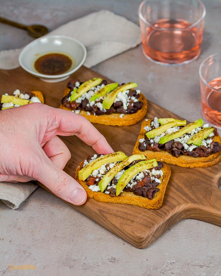 Close up with one hand reaching the black bean crostini from the wooden board. Spoonabilities.com