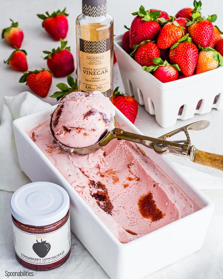 Homemade strawberry ice cream in a white container with a scoop with ice cream. Next to the container in the lower left side a jar of strawberry lemongrass spread by brims and in the upper right side a bottle of white balsamic vinegar by Navarion Icons. In the background a basket with fresh strawberries. Spoonabilities.com