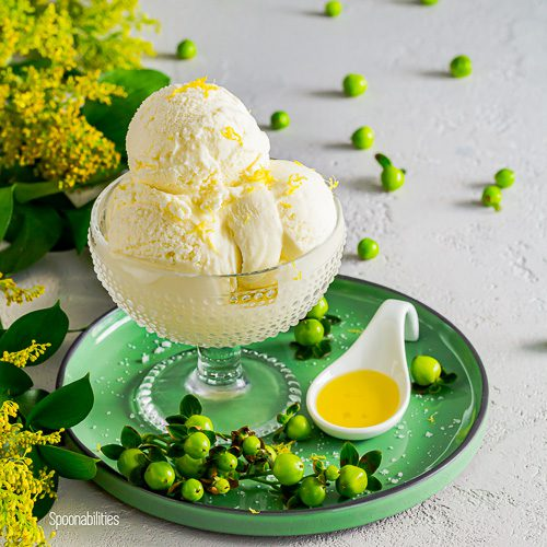 Green round plate and on top a glass dessert cup with homemade olive oil ice cream and a small ceramic spoon with LIA extra virgin olive oil. In the left side green leaves and tiny yellow flowers. Spoonabilities.com