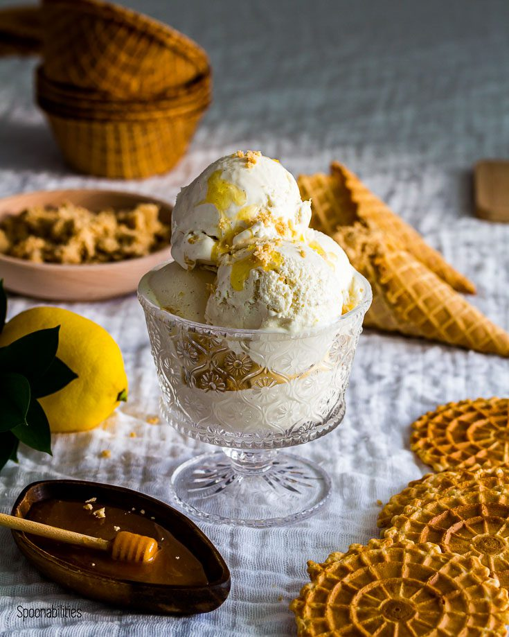 homemade ice cream topped with sesame halva an honey in a glass cup with waffle cones in the background. Spoonabilities.com