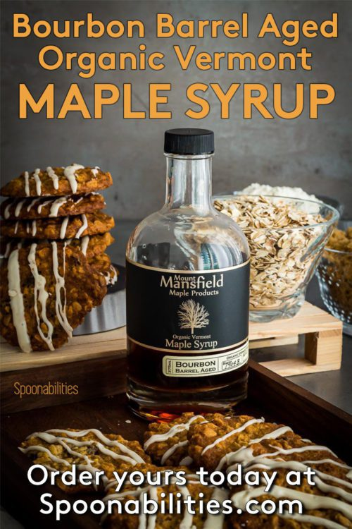 Bottle of Organic Bourbon barrel aged Vermont Maple Syrup surrounded by Oatmeal Raisin Cookies