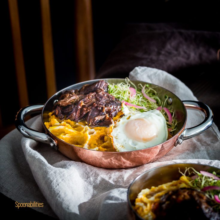 Fall inspired recipes with tender short ribs braised in brandy in the pressure cooker served in a personal cooper fry pan with two handles with Mashed Pumpkin-Cauliflower with brown butter, fried egg, Alfalfa Sprouts & pickled red onions. Spoonabilities.com