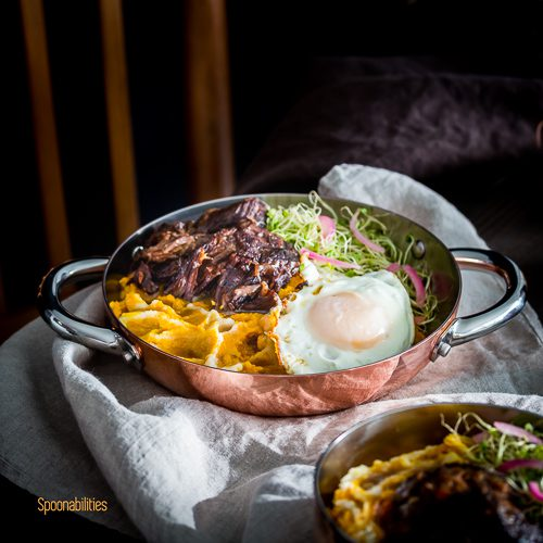 mouthwatering braised Short Ribs served in a personal saucepan. Garnished with crispy friend egg, Alfalfa Sprouts and pickled red onions. Spoonabilities.com