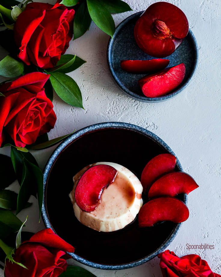 Panna Cotta with red wine syrup in a round blue plate with red roses around the plate with another plate in the uppper side of the photo with plumcots slices. Spoonabilities.com