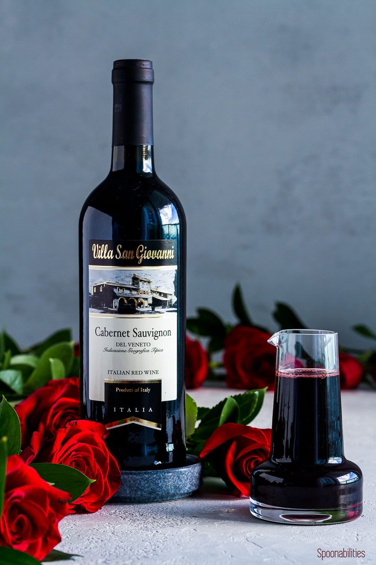A bottle of Cabernet Sauvignon from Villas San Giovanni on top of a small blue saucer with red roses around the wine. In another small carafe the red wine syrup. Spoonabilities.com