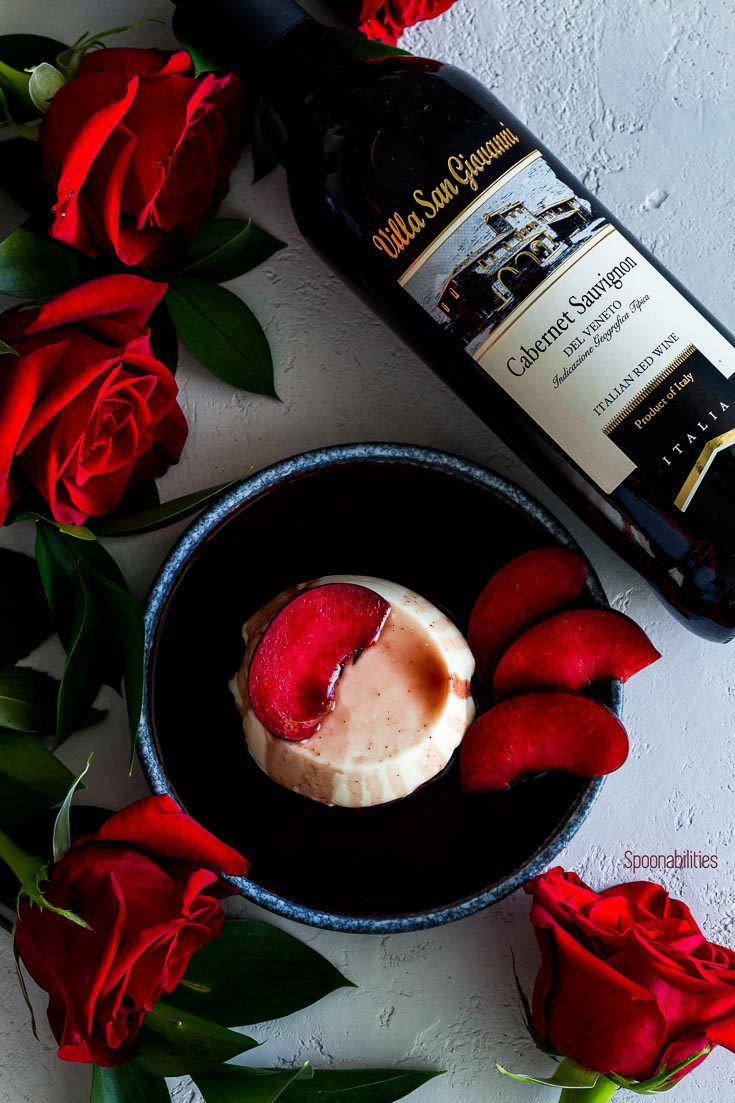 Lay flat photo with panna cotta in a round blue plate surrounding red roses and a bottle of Villas San Giovanni Cabernet Sauvignon. Spoonabilities.com