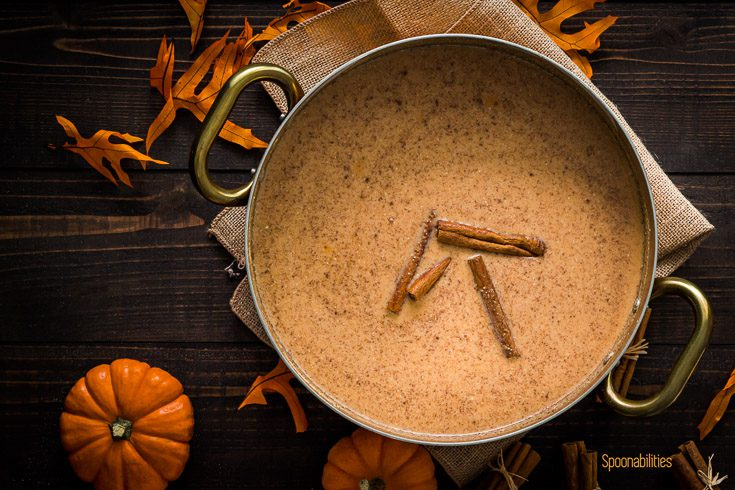Pot with a mixture of brown butter, cornmeal, whole milk, coconut milk, evaporated milk, pumpkin puree, salt, sugar, & pumpkin spice mix. The scene is decorated with Fall decor. Spoonabilities.com