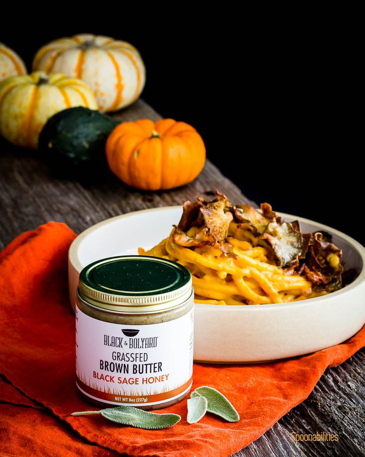 A jar of Grassfed brown butter with black sage honey in front of a pasta bowl. Spoonabilities.com