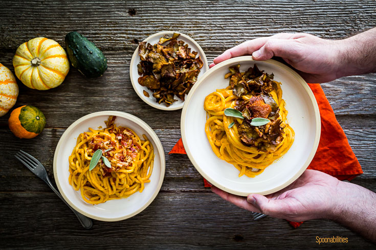 Two hands holding a bowl with pasta coated in creamy pumpkin pasta sauce and topped with crispy oyster mushrooms. two more plates on the far left of the table. Spoonabilities.com
