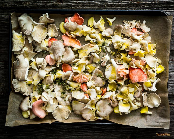 Baking tray with mixed oyster mushroom seasoned with olive oil, garlic & thyme. Spoonabilities.com