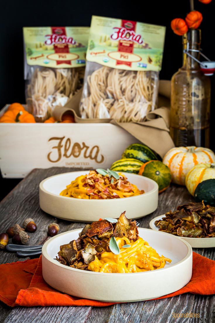 Two bowl of pasta and in the background a wooden basket with two pici pasta bags from Flora Fine Foods. Spoonabilities.com
