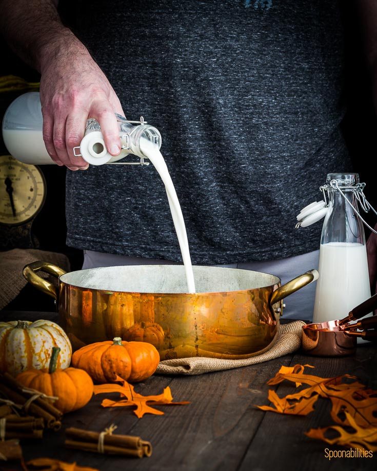 Pouring milk in a cooper pot. The scene is decorated with fall decor. Spoonabilities.com