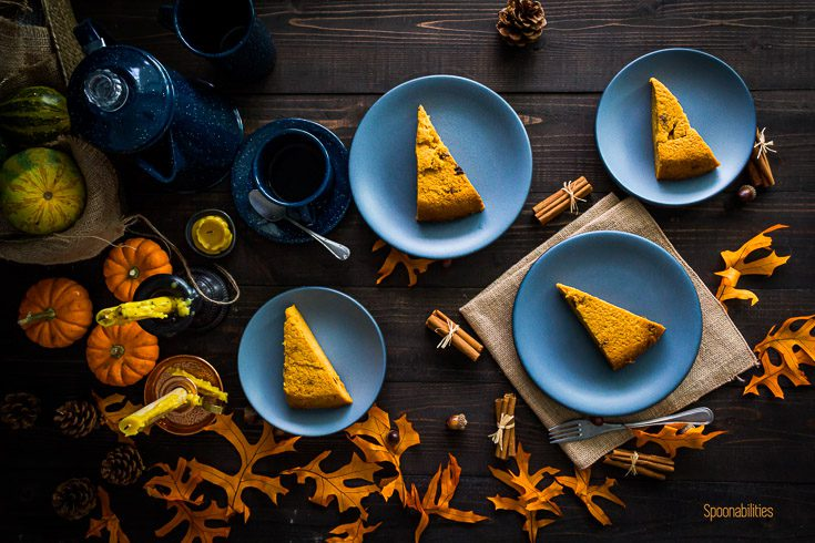 Four small blue plate and each of them with Pumpkin Cornmeal Coconut Cake. The background with fall decor. Spoonabilities.com