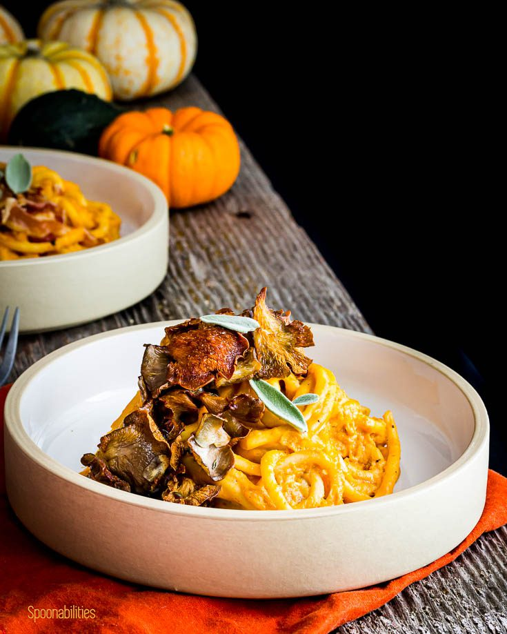 Pasta bowl with pici pasta tossed with pumpkin pasta sauce and topped with crispy oyster mushrooms. Spoonabilities.com