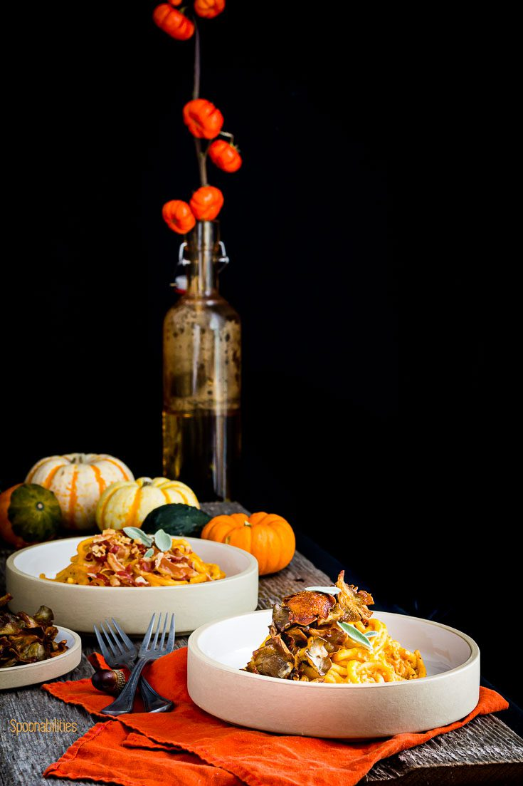 Table set up with two pasta bowl and decorated with pumpkin and Fall decor. Spoonabilities.com