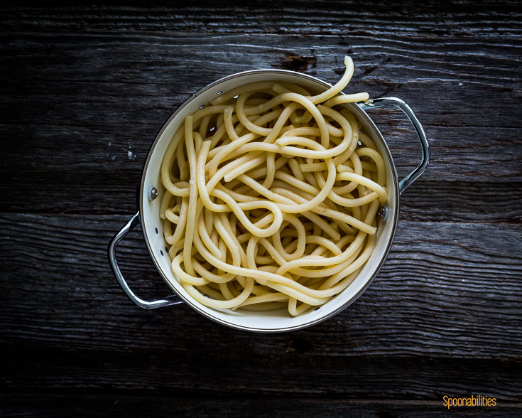 Cooked pici pasta in a white colander on a wooden surface. Spoonabilities.com
