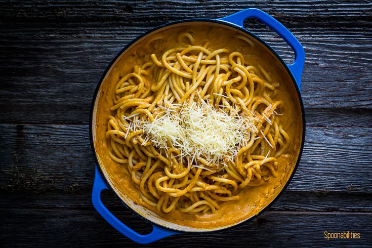 Pasta mixed with pumpkin pasta sauce with Parmesan cheese in a blue cast iron pan. Spoonabilities.com