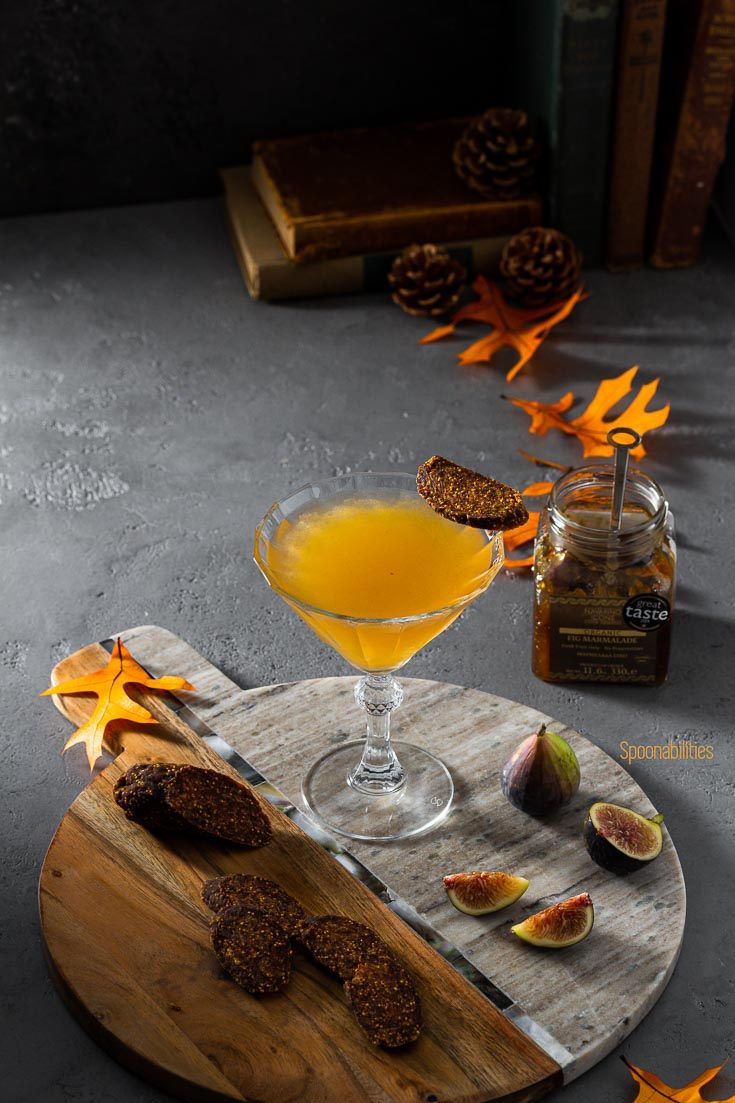Fig Martini in a beautiful glass on a serving board. Next to the board a jar with a brown label with Fig Marmalade Organic Navarino Icons. The acacia marble board is garnished with fresh fig and slices of vegan fig salami. Spoonabilities.com