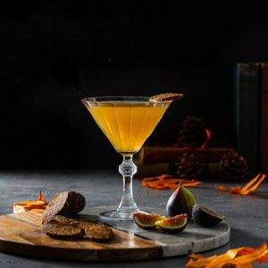 Recipe of a Fig Vodka Martini in a vintage cocktail glass on top of a serving board with fall decoration, fresh fig and vegan fig salami. available at spoonabilities.com