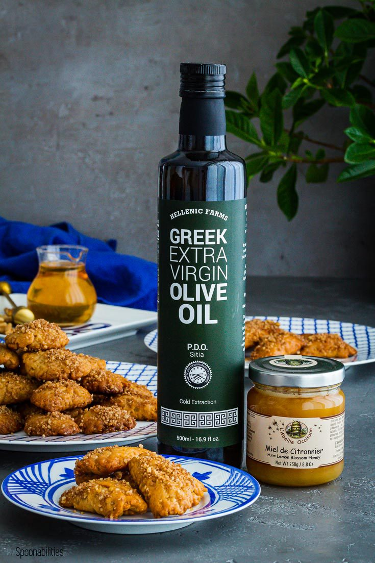 A small plate with three cookies and next to the plate a large bottle of Hellenic Farms extra virgin olive oil PDO Sitia and a jar of French honey. Spoonabilities.com