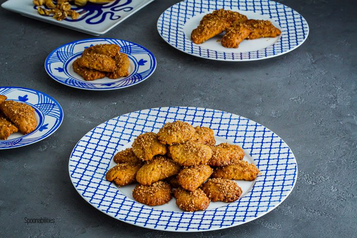 White and blue plate with Greek Christmas cookies and three more plates in the background with cookies. Spoonabilities.com