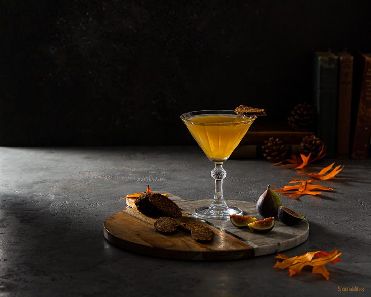 Horizontal photo with a beautiful Vintage cocktail glass on a round board with a Fig martini made with fig jam from Navarino Icons and vodka. Garnished with a slice Vegan Fig Salami. The marble acacia board has fresh fig and a slices of the vegan fig salami. Available at Spoonabilities.com