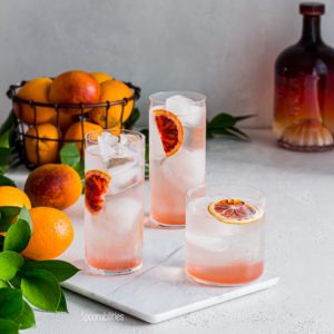 Three Blood Orange Vodka Sodas on a marble cutting board with bottle of Salerno in background