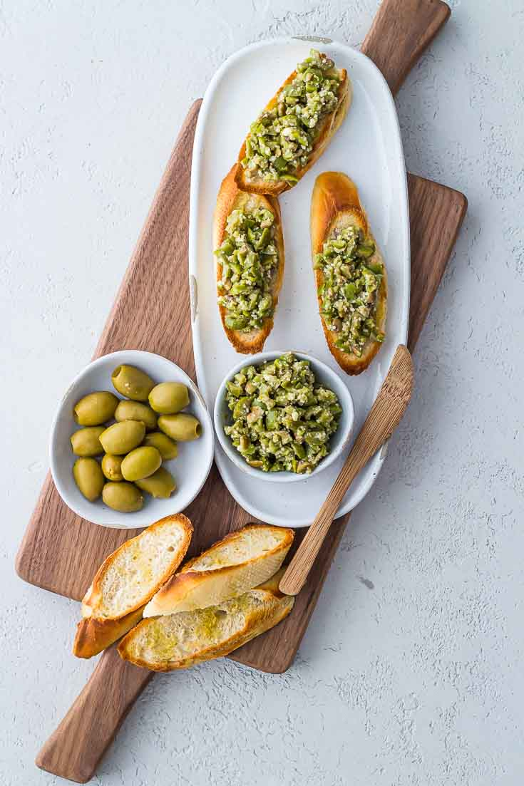 Overhead shot of 3 Greek Olive Crostini on a white plate next to green olives and baguette slices