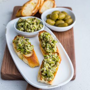 Three servings of Greek Olive Crostini on a white plate