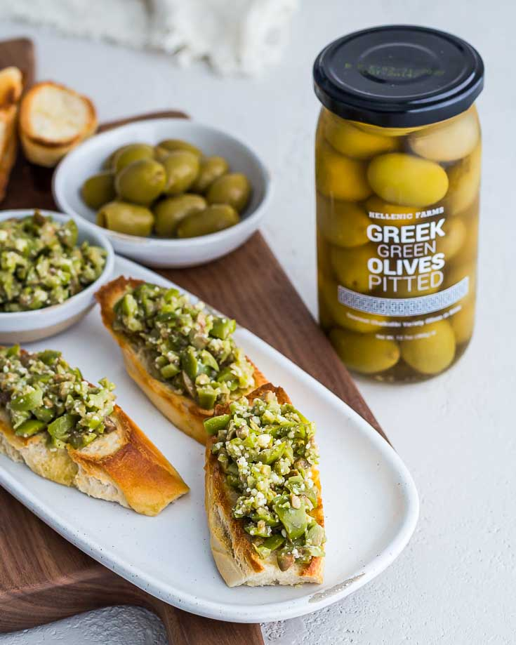 Three servings of Greek Olive Crostini on a white plate next to a jar of Greek Green Olives