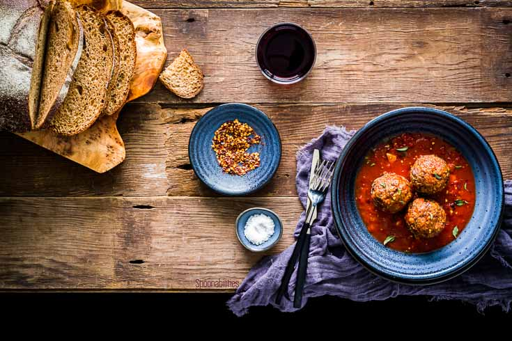 Overhead photo with one bowl with three Jumbo Brisket Meatballs in San Marzano tomato sauce. Next to the bowl two small saucer one with sea salt and the second one with smoked chili pepper and in the right top corner a loaf of bread. Spoonabilities.com
