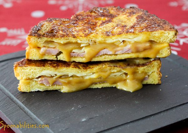 two slices of Monte Cristo sandwiches stacked on top of each other with cheese dripping out the side. Spoonabilities
