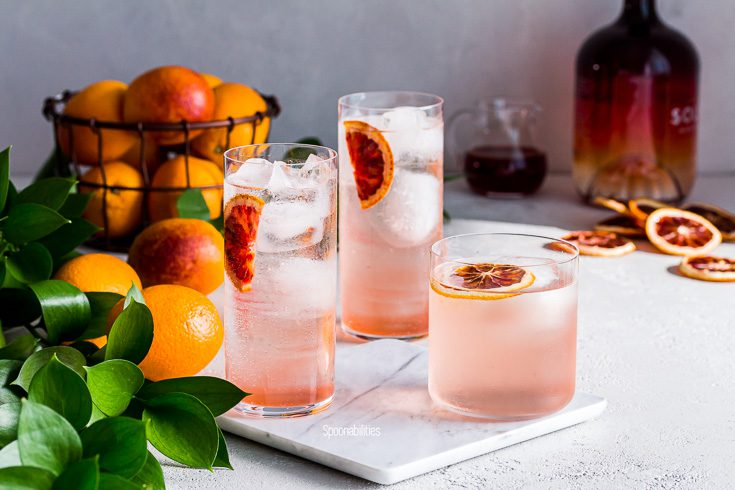 Three Vodka Blood Orange Sodas on a marble cutting board with bottle of Salerno in the background