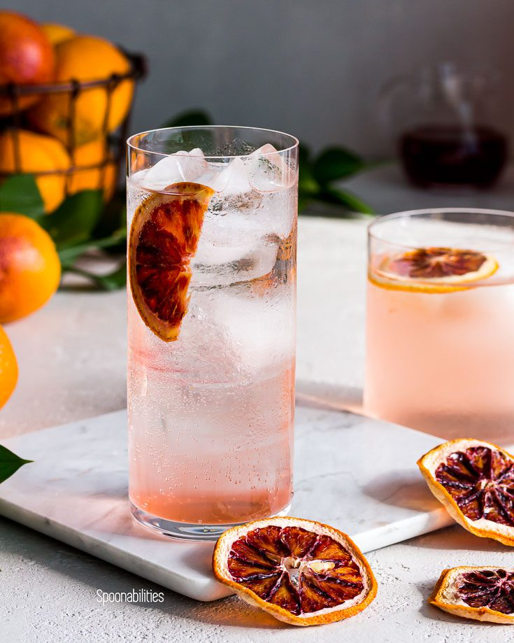 closeup of a tall glass of a blood orange vodka soda sitting on a marble tray