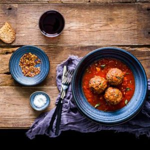 Three meatballs in a blue bowl with two small saucers with condiments on the left side. Spoonabilities.com
